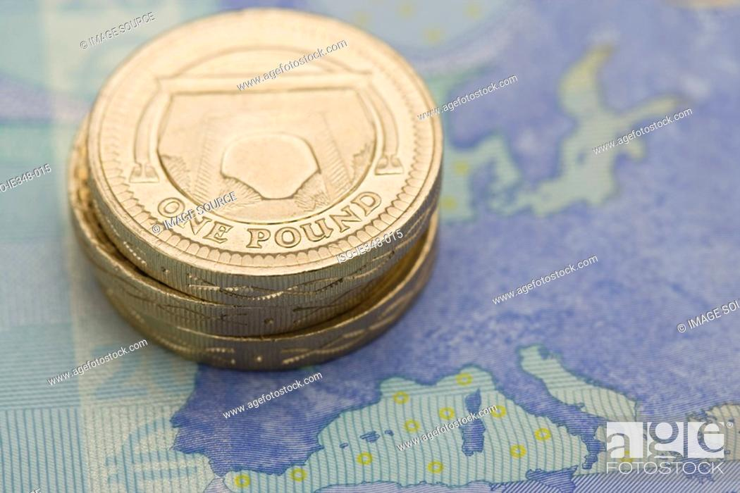 Stock Photo: Pound coins on euro note.