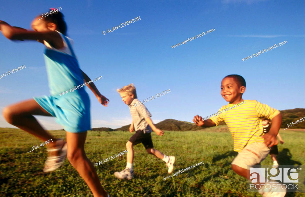 Stock Photo: Interracial group of boys and girls run past.