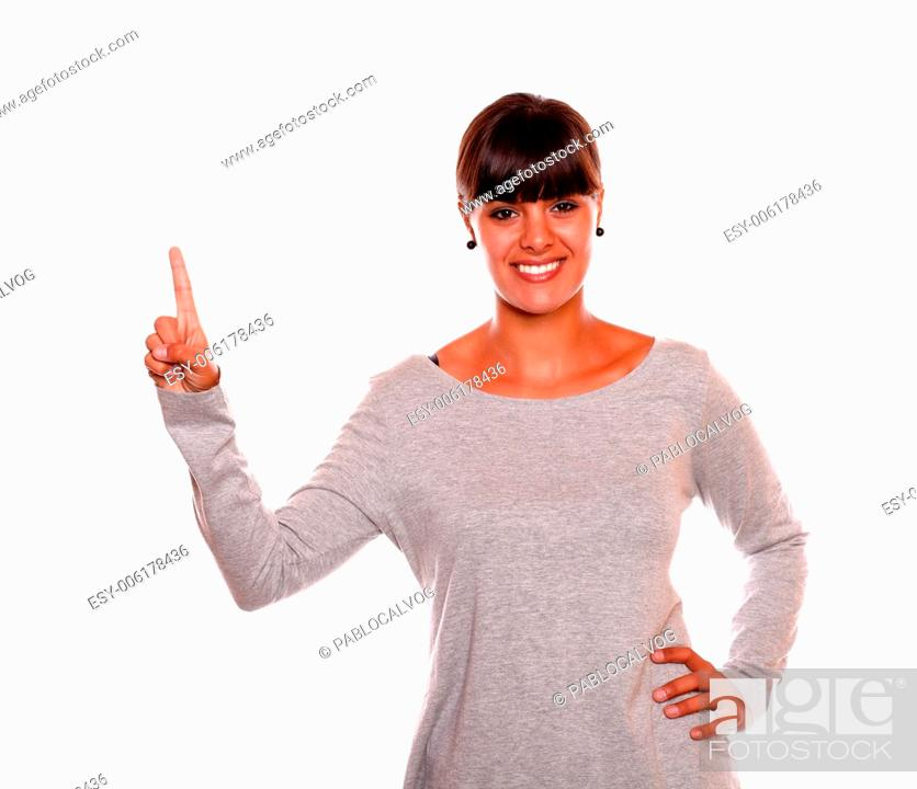 Stock Photo: Smiling young female on grey dress pointing up standing over white background - copyspace.