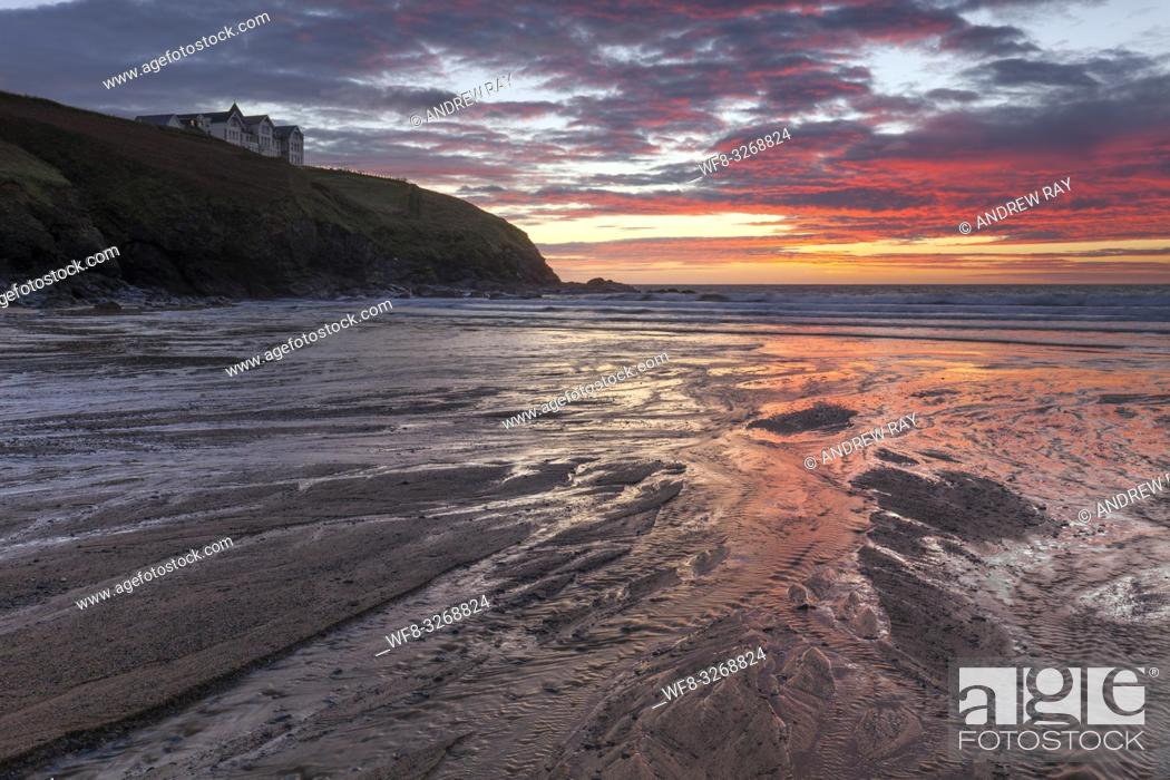 Stock Photo: Sunset reflected in the river on Poldhu Cove beach on Cornwall's Lizard Peninsula, with the former Poldhu Cove Hotel in the distance.