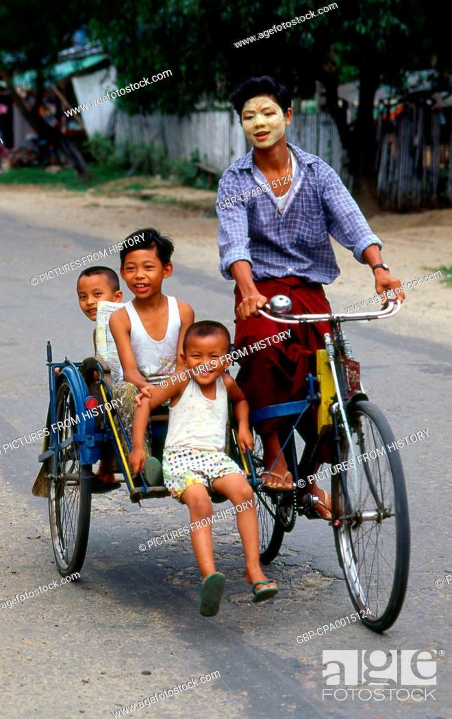 Burma / Myanmar: Three Bamar children riding a bicycle
