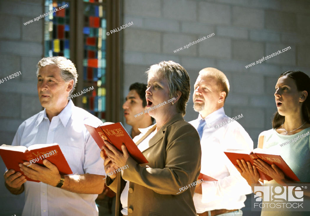 Stock Photo: Five People Holding Hymn Books and Singing in a Church Congregation.