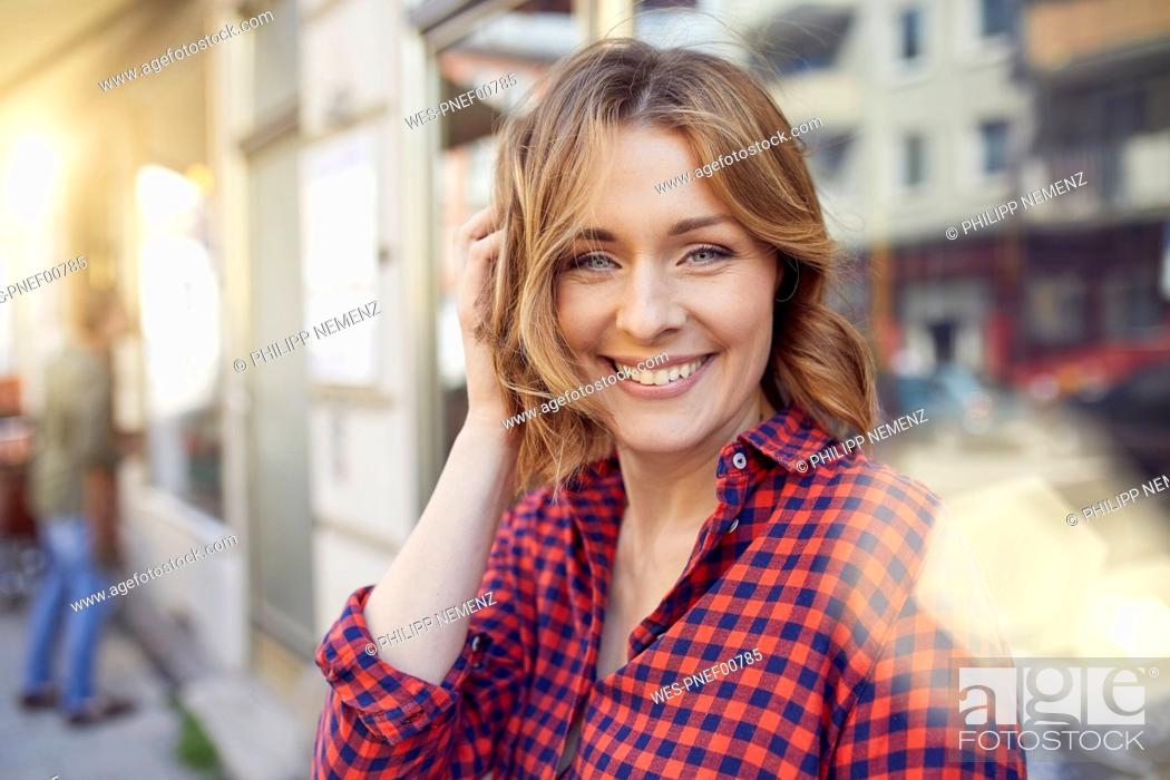 Stock Photo: Portrait of smiling woman in the city.