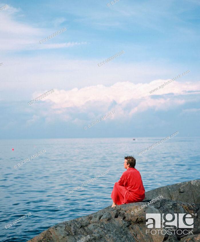 Stock Photo: Boy looking at sea with bathrobe. Landsort Island. Sweden.