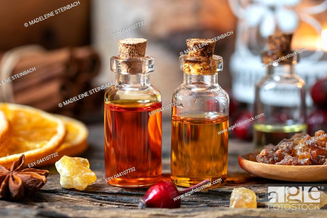 Stock Photo: Christmas collection of essential oils with myrrh, frankincense, rose hips and star anise.