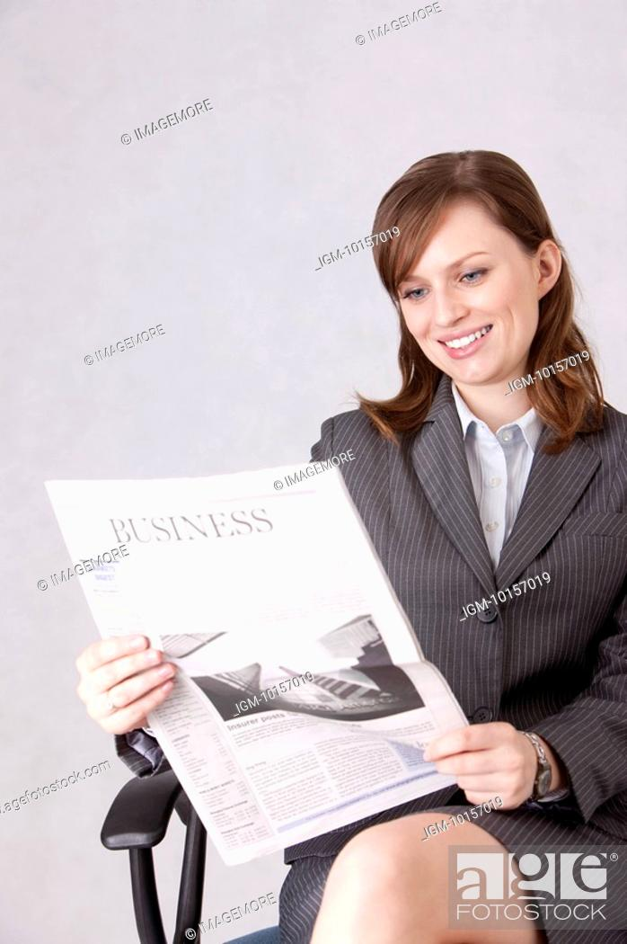 Stock Photo: Businesswoman sitting in a chair and reading a newspaper with smile.