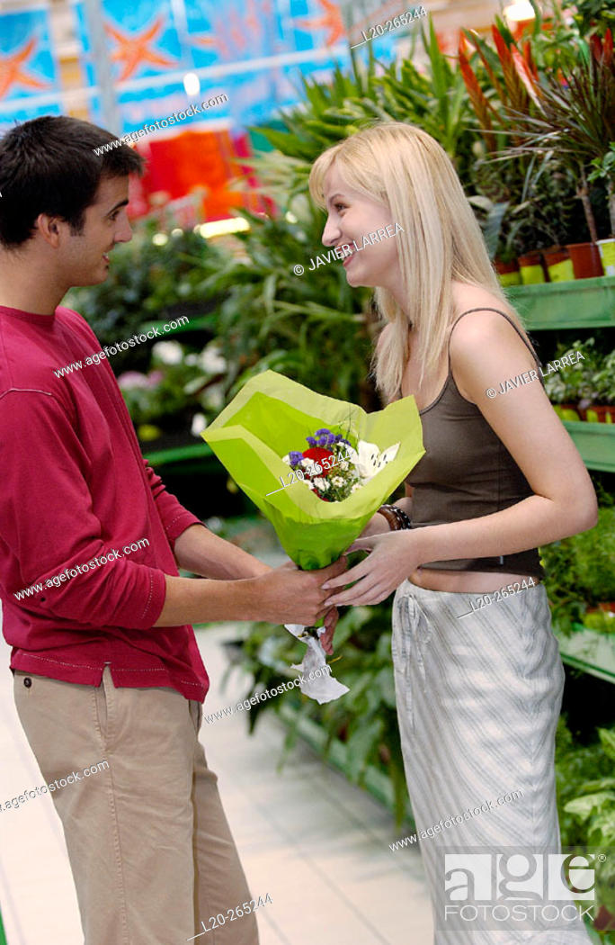 Stock Photo: Couple with flower bouquet at shopping center.