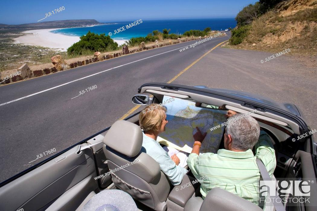 Stock Photo: Mature couple looking at map in car.