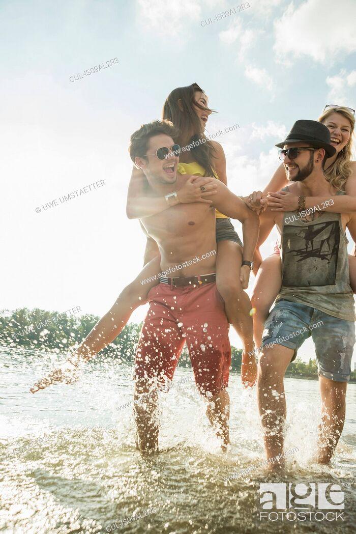 Stock Photo: Young men giving young women piggy backs.