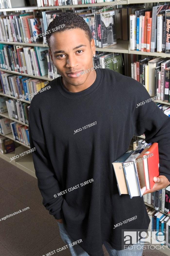 Stock Photo: Young man holding books underarm in Library.