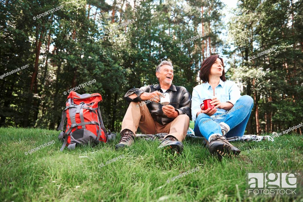 Stock Photo: Mature couple relaxing on grass, holding tin cups, rucksack beside them.