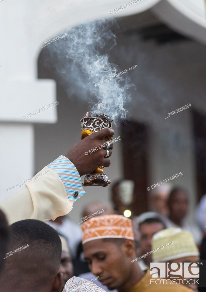 Stock Photo: Sunni muslim man spreading insence with a censer during the Maulidi festivities in the street, Lamu County, Lamu Town, Kenya.