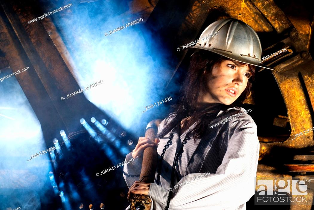 Imagen: Representation of work in a mine made with a beautiful young woman with an aluminum hull pulling a steel cable with stained face and a dramatic lighting.