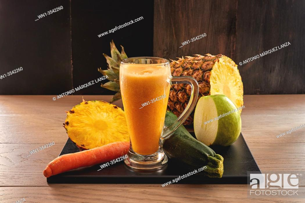 Stock Photo: veggie juicy of pineapple, apple, cucumber and carrot in a dark background.