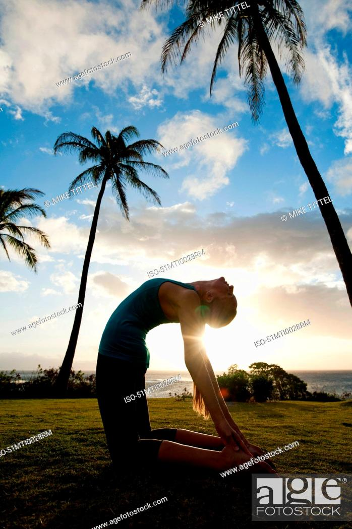 Stock Photo: Woman practicing yoga in grassy field.