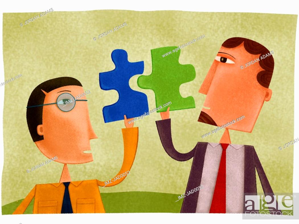 Stock Photo: Two businessmen holding puzzle pieces that fit together.