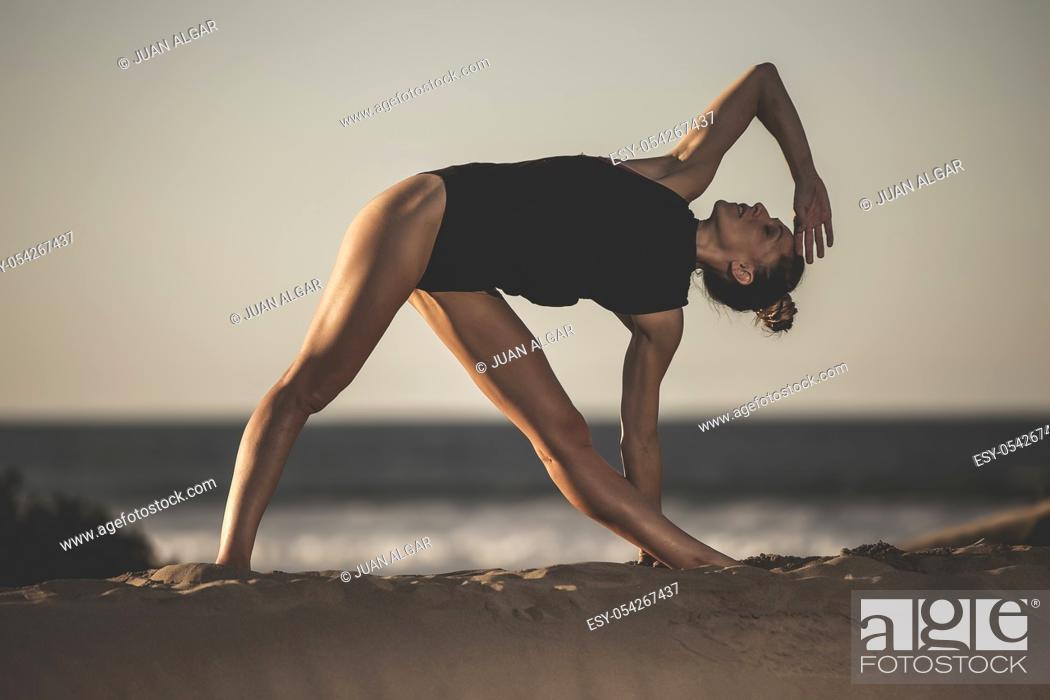 Stock Photo: Beautiful sensual woman in black bodysuit showing yoga posture on beach in sunlight.