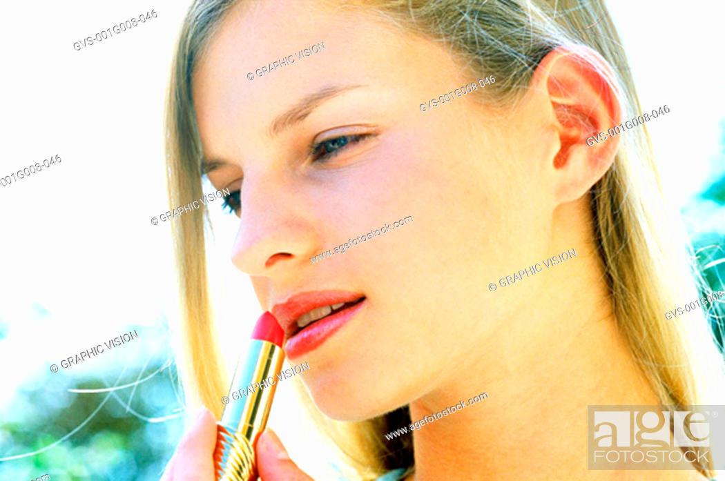 Stock Photo: Young woman applying lipstick.