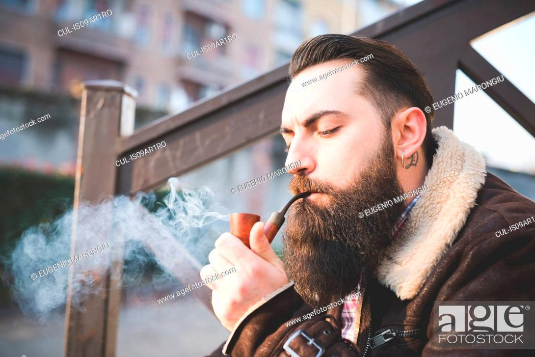 Stock Photo: Young bearded man smoking pipe on steps.
