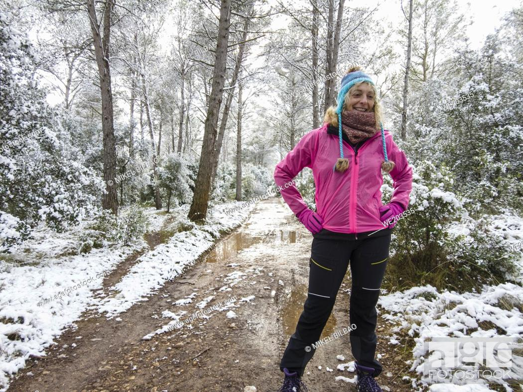 Imagen: Caucasian young woman with a hat enjoying snow outdoor in a path in a forest area in winter time. Navarre, Spain, Europe.