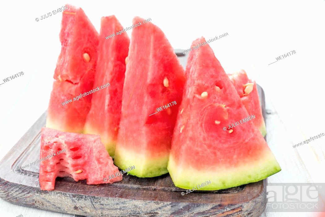 Photo de stock: lots of watermelon on white wooden board.