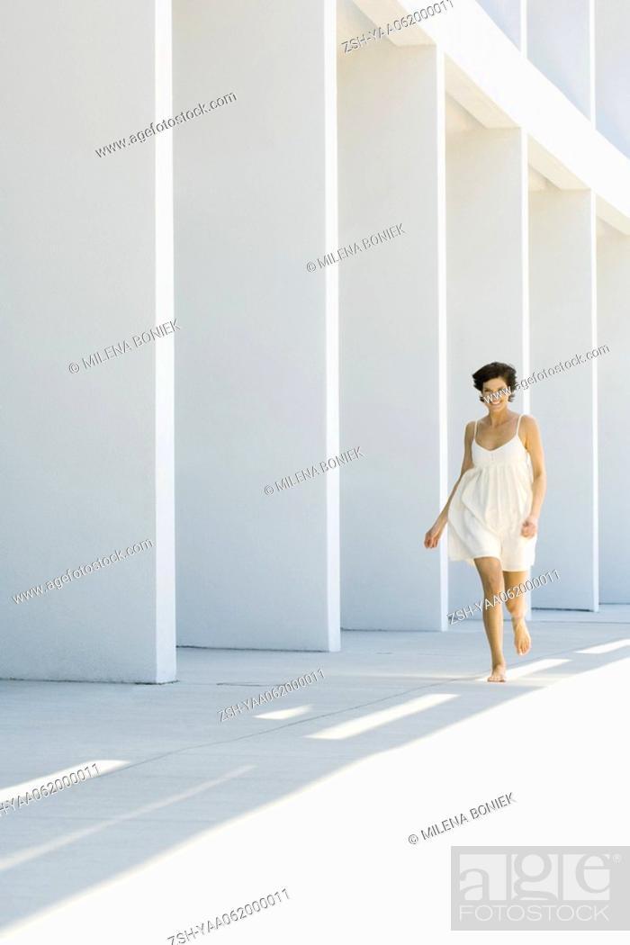 Stock Photo: Woman in sundress running outdoors, full length.