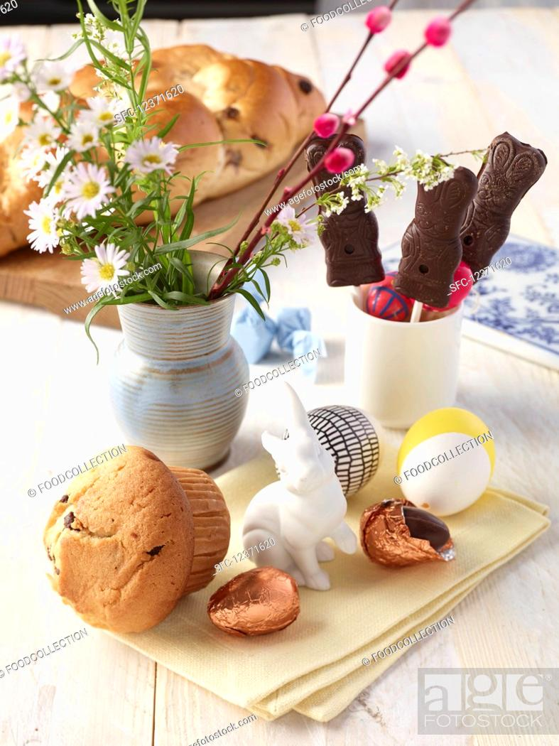 Stock Photo: Vegan Easter bread, chocolate rabbits, chocolate eggs and a bouquet of flowers.