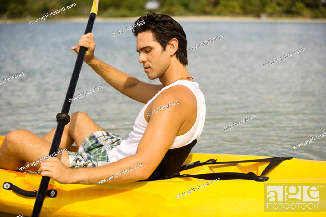 Stock Photo: Side profile of a young man kayaking in a lake.