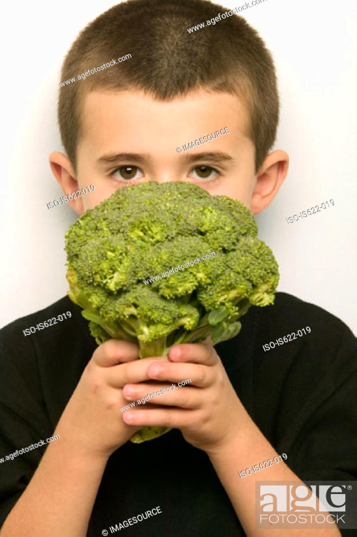 Stock Photo: Boy covering face with broccoli.