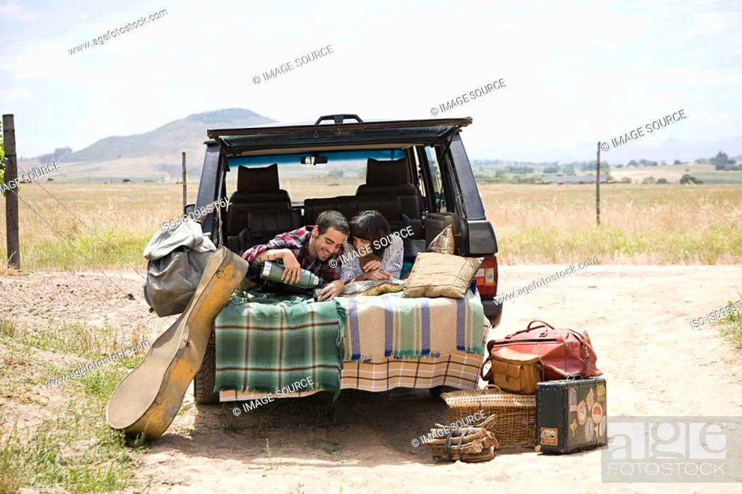 Stock Photo: Couple relaxing in back of suv.