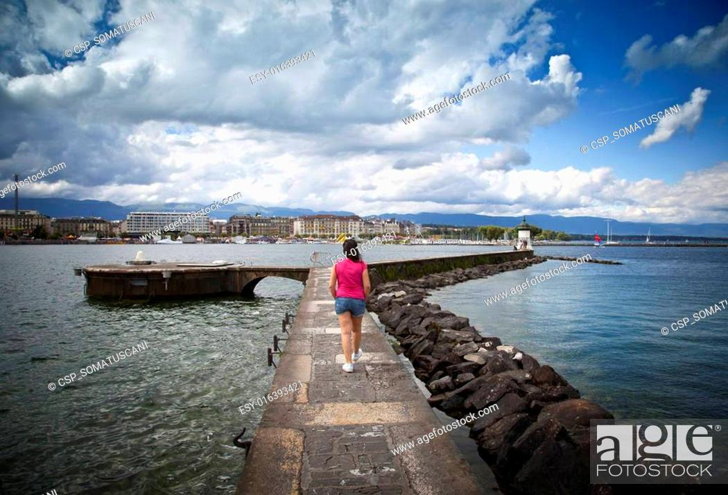 Stock Photo: Young woman walking in the Jet d'Eau dock in Geneva.
