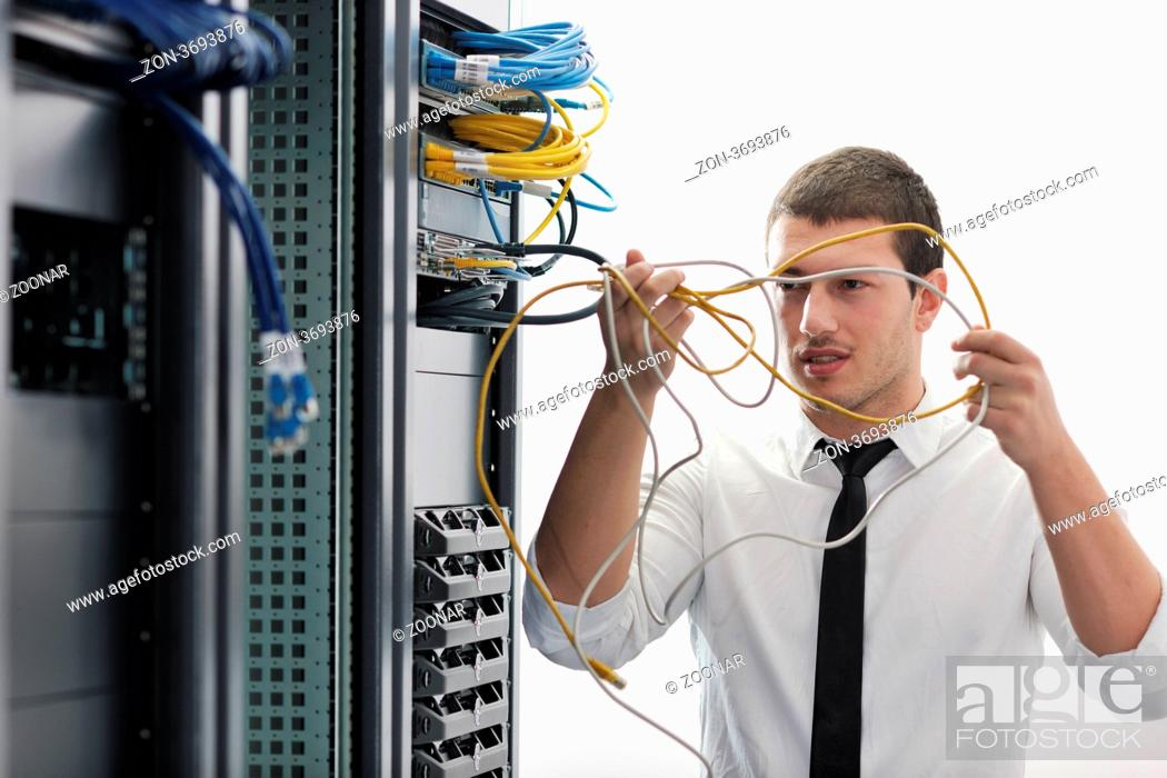 Stock Photo: young handsome business man it engeneer in datacenter server room.