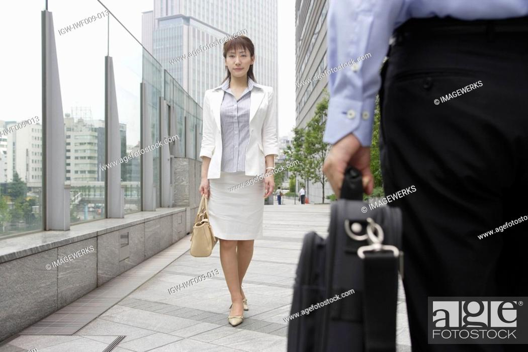 Stock Photo: A formally dressed woman walking on the bridge with a bag.