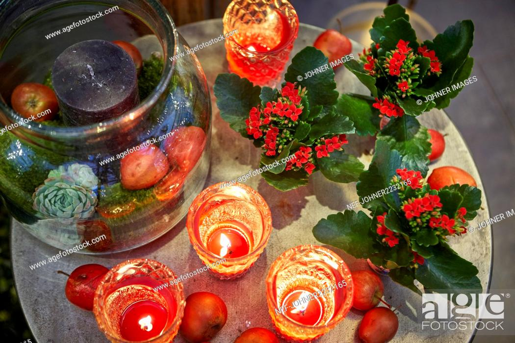 Stock Photo: Red candles and flowers on table.