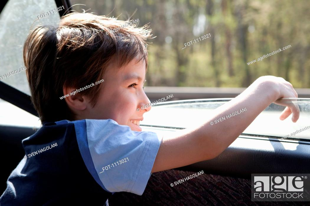 Stock Photo: A child looking out a car window.