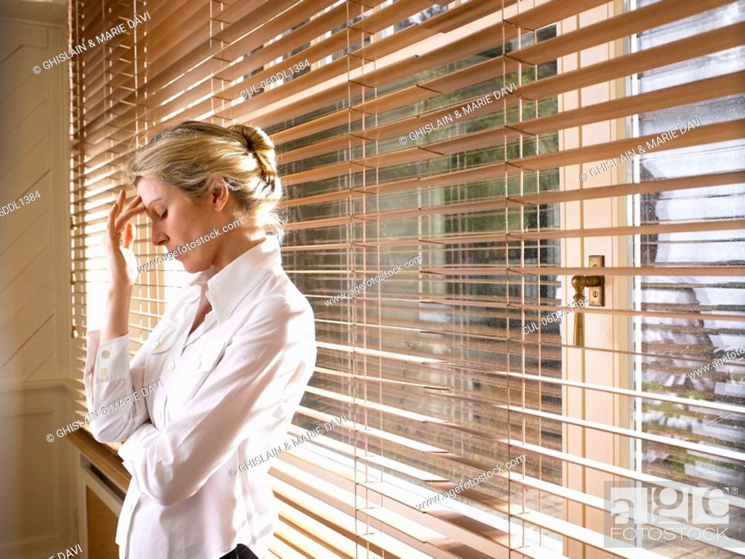 Stock Photo: Woman standing by the window.