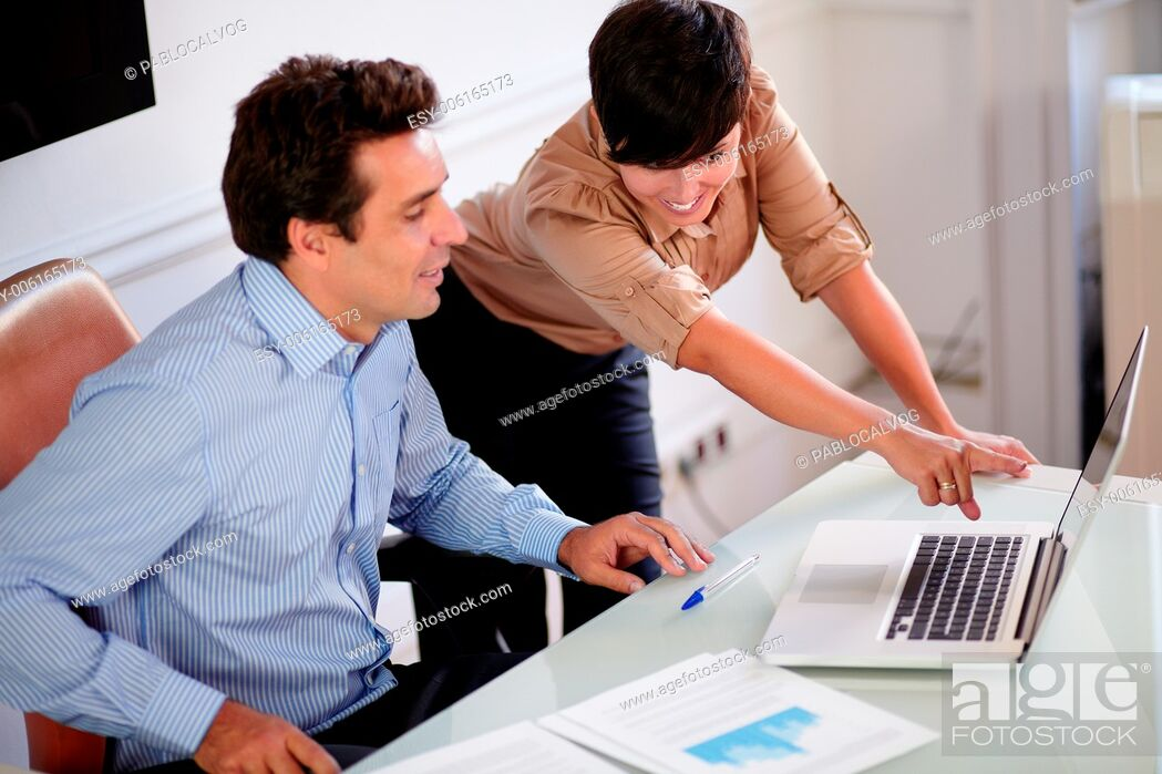 Stock Photo: Portrait of an attractive manager talking with his secretary while looking at laptop on office desk.