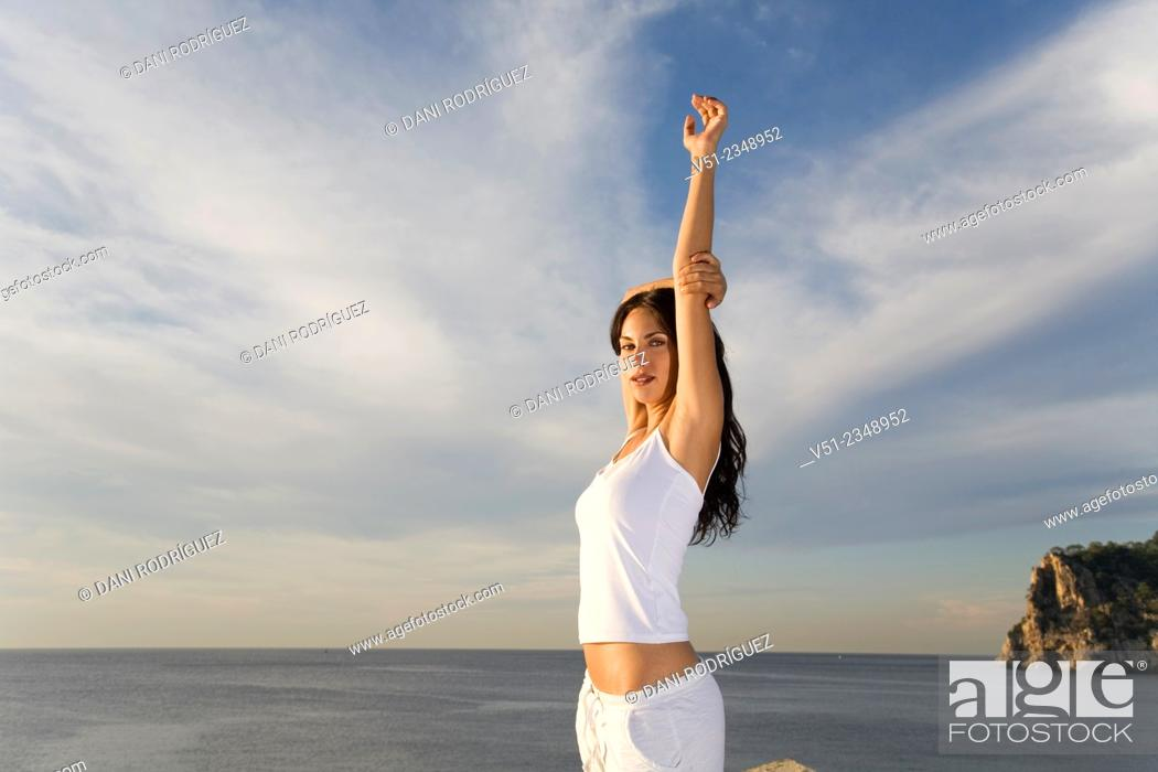 Stock Photo: Portrait of a brunette woman breathing fresh air by the sea smiling at camera.