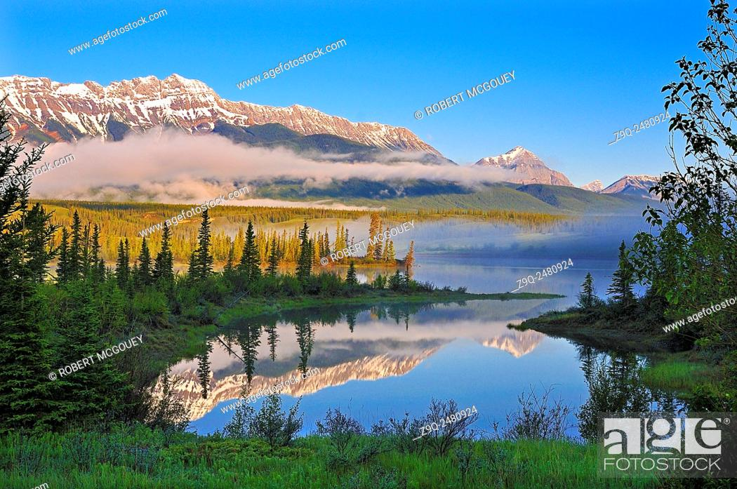 Stock Photo: A horizontal landscape image of the majestic Rocky Mountains reflecting in the still waters of the Athabasca River with an early morning mist hanging over the.