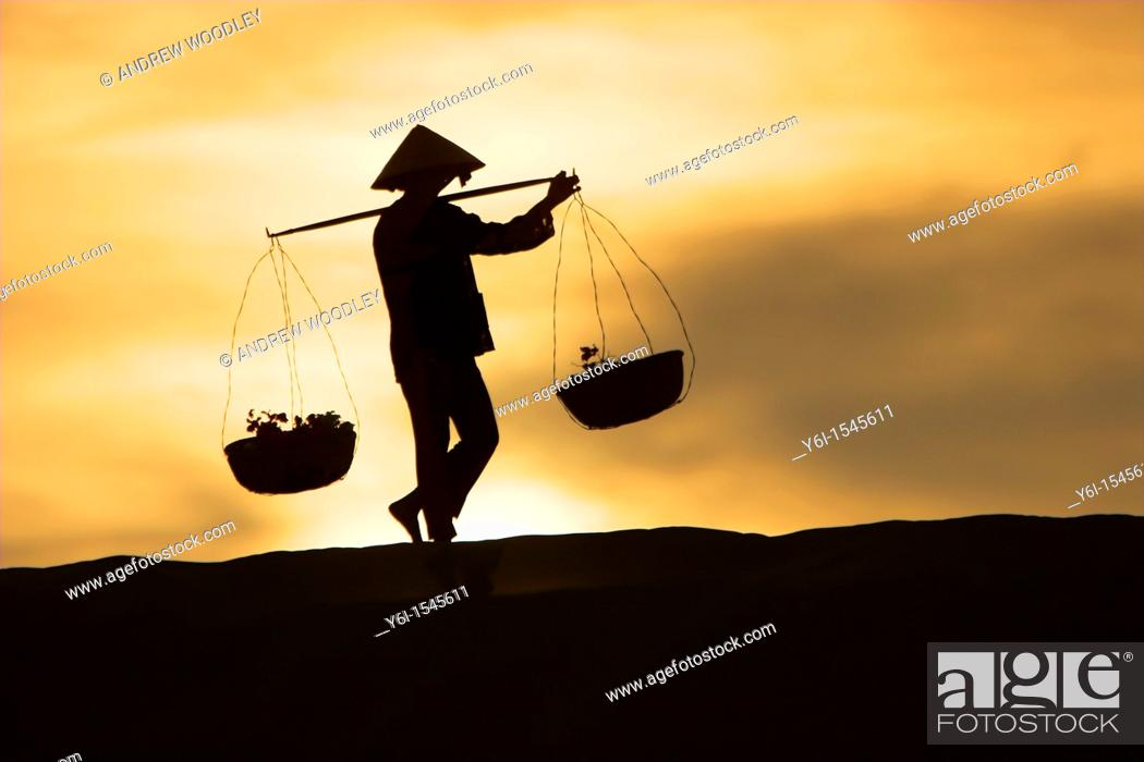 Stock Photo: Woman with conical hat carries pannier baskets in sunrise along crest of sand dunes near Mui Ne Vietnam.