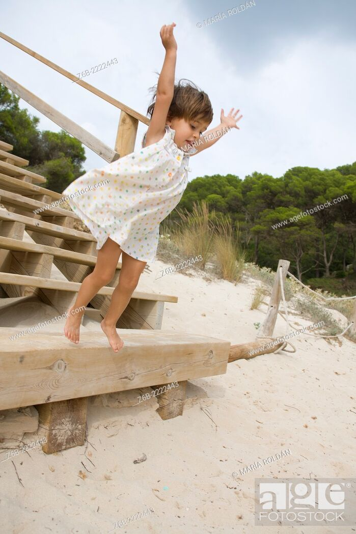 Stock Photo: Almost 3 years old little girl jumping from a stair on a beach in Menorca, Spain.