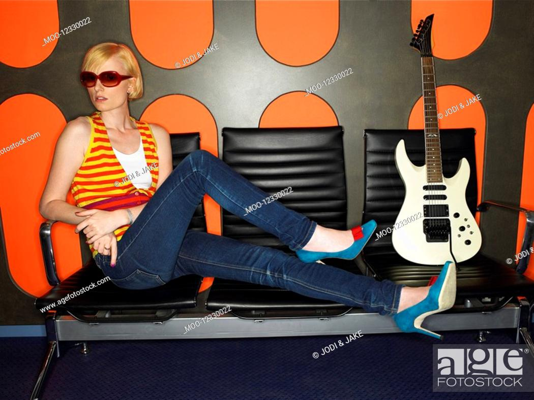 Stock Photo: Young woman with guitar in recording studio portrait.