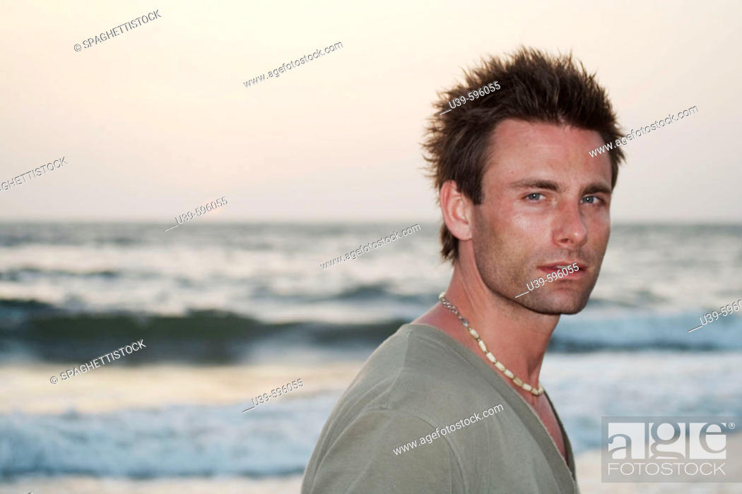 Stock Photo: Horizontal shot of a good-looking man in a green t-shirt next to the Indian ocean with the sun setting.