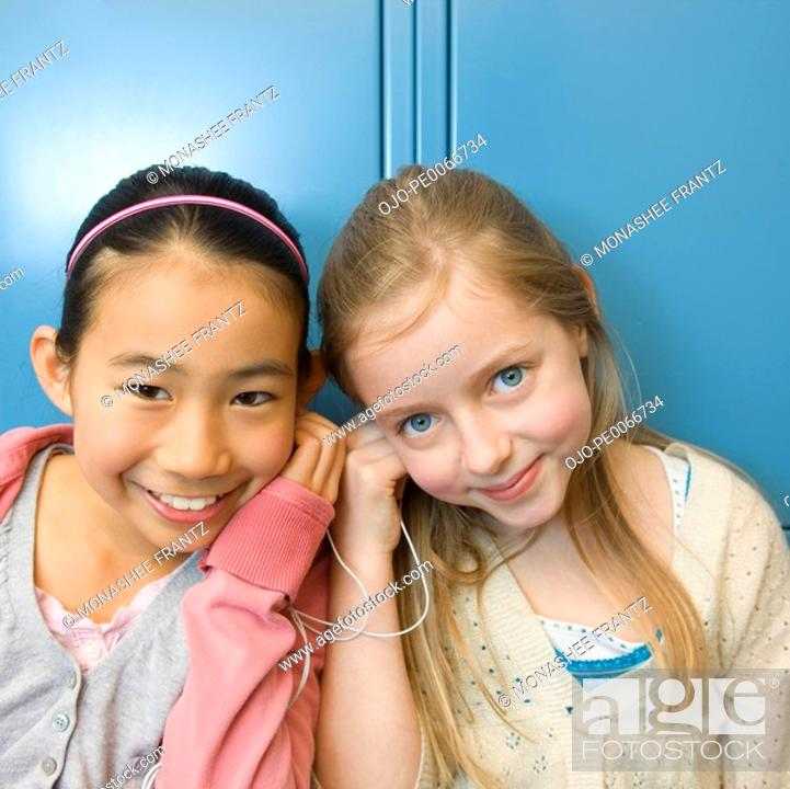 Stock Photo: Girls listening to mp3 player in school hallway.