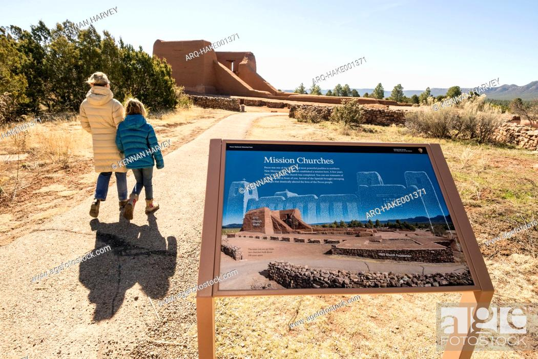 Stock Photo: Mother and daughter walking past information sign in Pecos National Historical Park on sunny day, Pecos, New Mexico, USA.
