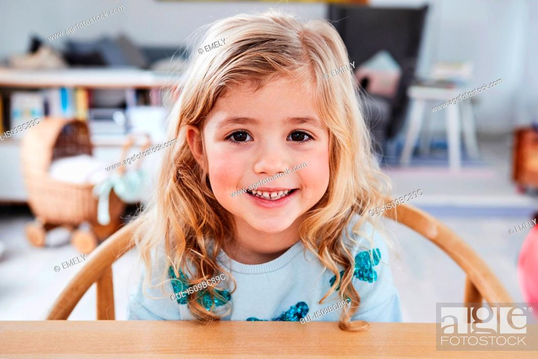 Stock Photo: Portrait of young girl, sitting at table, smiling.