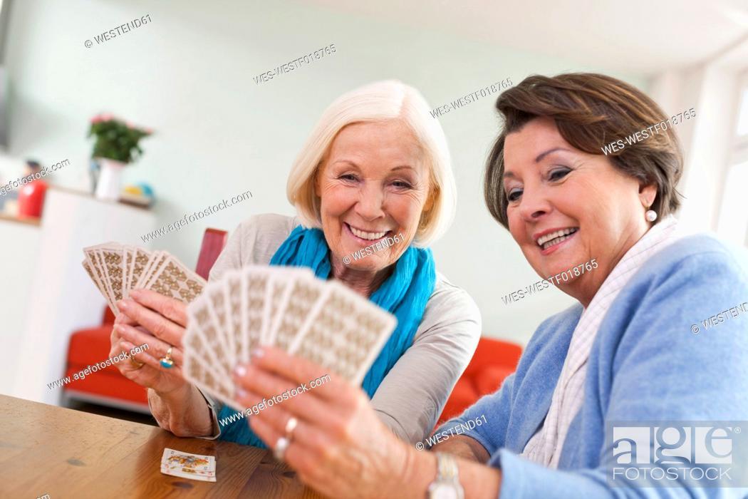 Stock Photo: Germany, Leipzig, Senior women playing card game, smiling.