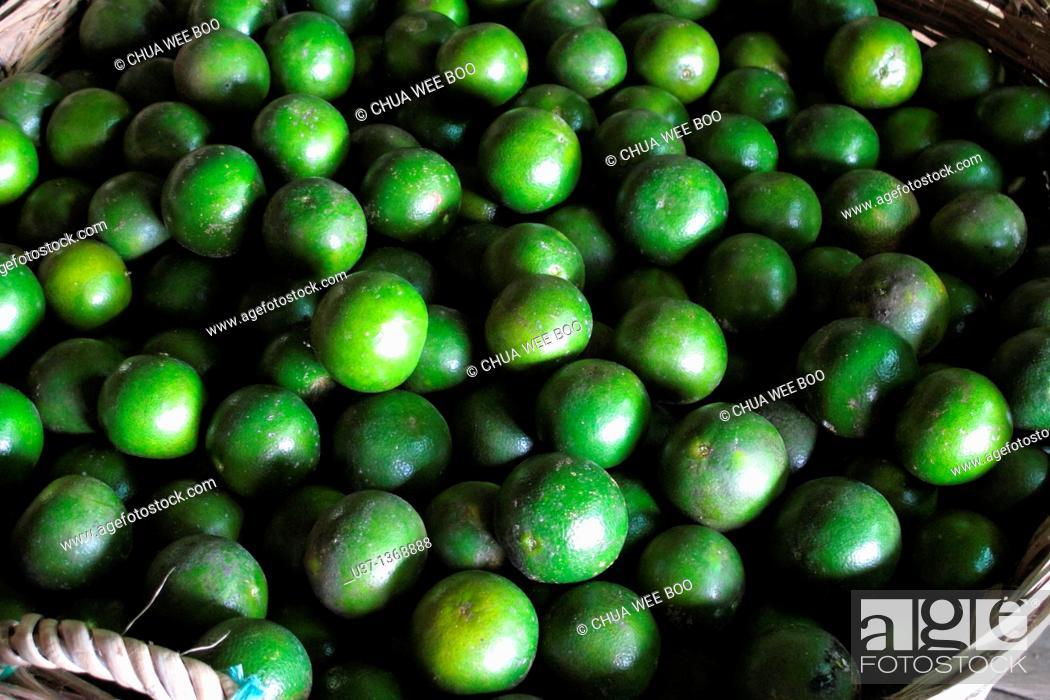 Stock Photo: Baskets of green oranges stored at Kampung Semparuk, Western Kalimantan, Indonesia.