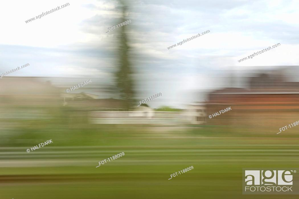 Stock Photo: A village in blurred motion viewed from a moving train.