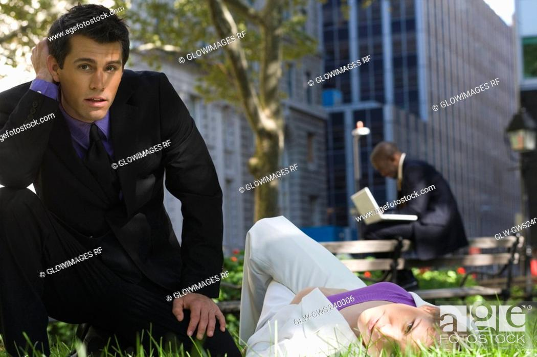 Stock Photo: Portrait of a young woman lying on grass in a park with a businessman beside her.